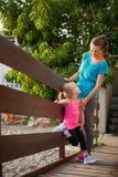 Junge Mutter und Tochter, die auf einer Holzbrücke auf Strand steht Lizenzfreie Stockbilder