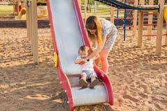 Junge Mutter und Vater, die mit ihrem Baby auf dem Spielplatz spielt lizenzfreies stockfoto