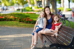 Junge Mutter und zwei nette kleine Schwestern, die auf einer Bank umarmt am warmen und sonnigen Sommertag sitzen Stockbild