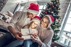 Junge Mutter, Vater und kleine Töchter, die ein magisches Weihnachtsgeschenk öffnen stockbild