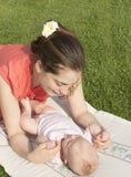 Junge Mutter verständigt sich mit dem Baby. Stockfoto