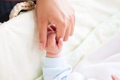 Junge Mutter, welche die Hand ihres Schätzchens anhält Lizenzfreie Stockfotografie