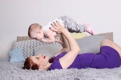 Junge Mutter zieht ihr kleines Baby auf Bett auf Lizenzfreie Stockfotografie