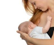 Junge Mutterfrau, die ihr Kinderbaby stillt Stockfotografie