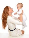 Junge Mutterfrau, die in ihrem Armsäuglingskinderbabykind hält Stockfotografie
