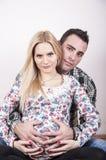 Junge Muttergesellschaft, die Bauch umarmen Lizenzfreie Stockbilder