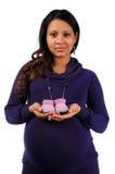 Junge Mutterholding strickte Babyschuhe Stockfoto