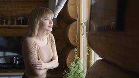 Junge nachdenkliche Frau, die durch ein Fenster schaut Stockbilder