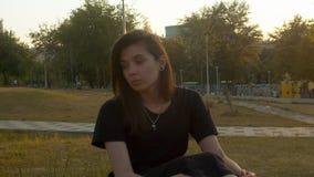 Junge nachdenkliche Frau, die im Park sitzt stock footage