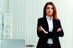 Junge nachdenkliche Geschäftsfrau, die mit den Armen gefaltet steht Stockbild