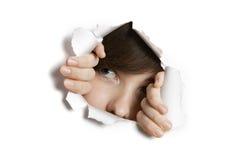 Junge nahöstliche Frau, die von zerrissenem Weißbuchloch späht Stockbild