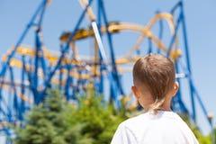 Junge nahe bei einer Achterbahn Stockfotografie
