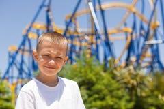 Junge nahe bei einer Achterbahn Lizenzfreies Stockfoto