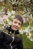 Junge nahe dem blühenden Baum Lizenzfreie Stockbilder