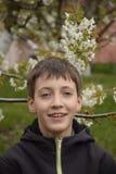 Junge nahe dem blühenden Baum Lizenzfreie Stockfotografie