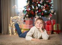 Junge nahe dem Weihnachtsbaum stockfotos