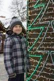 Junge nahe einem Weihnachtsbaum von den Girlanden Stockbild