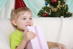 Junge nahe zum Weihnachtenc$pelzbaum sitzt mit Geschenk Stockbild