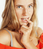 Junge nette blonde Mädchenaufstellung emotional auf dem weißen Hintergrund lokalisiert, Lebensstilleutekonzept Lizenzfreie Stockbilder