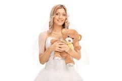 Junge nette Braut, die einen Teddybären hält Lizenzfreie Stockfotos