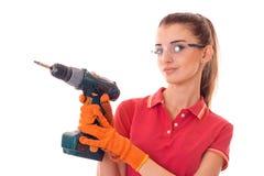 Junge nette Brunettefrau in der Uniform lässt Erneuerung mit ihre Hände herein bohren, welche die Kamera betrachten, die auf Weiß stockfotografie