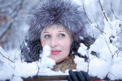 Junge nette Frau beim Waldlächeln des verschneiten Winters Lizenzfreies Stockfoto
