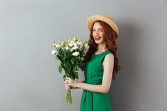 Junge nette Frau der Rothaarigen mit Blumen Stockbilder