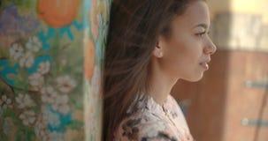 Junge nette Frau, die über schönem Wandgemälde aufwirft Lizenzfreie Stockbilder