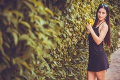 Junge nette Frau, die in einem grünen Park aufwirft Stockbilder