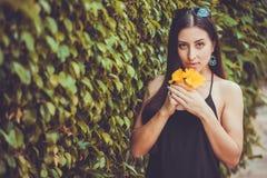 Junge nette Frau, die in einem grünen Park aufwirft stockfotografie