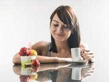 Junge nette Frau, die Eiscreme und Kaffee mit Reflexion schaut stockbilder