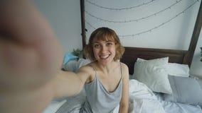 Junge nette Frau, die selfie Porträt unter Verwendung des Smartphone herein sitzt im Bett zu Hause nimmt stockfoto