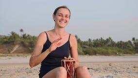 Junge nette Frau, die Trommeln auf sandigem Strand in der Zeitlupe spielt stock video footage