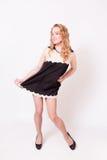 Junge nette Frau in einem schwarzen kurzen Kleid und in den hohen Absätzen Lizenzfreies Stockfoto