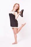 Junge nette Frau in einem schwarzen kurzen Kleid und in den hohen Absätzen in ihren Händen Lizenzfreies Stockbild