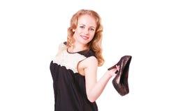 Junge nette Frau in einem schwarzen kurzen Kleid und in den hohen Absätzen in ihren Händen Lizenzfreie Stockfotos