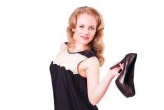Junge nette Frau in einem schwarzen kurzen Kleid und in den hohen Absätzen in ihren Händen Stockbild