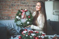 Junge nette Frau mit Weihnachtsimmergrünem Baum-Kranz lizenzfreies stockbild