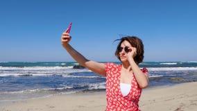 Junge nette Frau setzt ihre Sonnenbrille an und ein selfie Foto bei der Stellung machend auf den Sandstrand mit starken Wellen au stock video