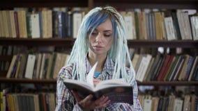 Junge nette Hippie-Frau mit Dreadlockslesebuch vor der Kamera im Bibliotheksraum stock video