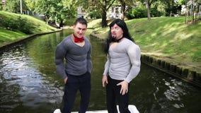 Junge nette Männer im gefälschtem Muskelkasten und -armen füllten Kostüme stehen im Boot auf stock video footage
