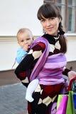 Junge nette Mutter mit Schätzchen im Riemen stockfotos
