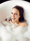 Junge nette süße Brunettefrau, die Bad, glückliches lächelndes Leutekonzept nimmt Lizenzfreie Stockbilder