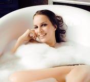 Junge nette süße Brunettefrau, die Bad, glückliches lächelndes Leutekonzept nimmt Stockfoto
