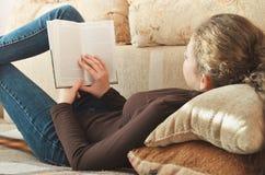 Junge nette Studentin, die ein Buch auf der Couch liest Stockfotos