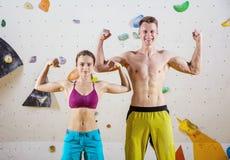Junge nette weibliche und männliche Kletterer, die Bizepse biegen stockfotografie