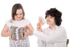 Junge nimmt einen Stapel des Geldes vom Mädchen weg Stockfotos