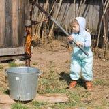 Junge nimmt Wasser von einem gut innen Dorf (1) Stockfotografie