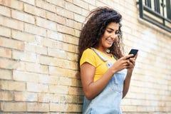 Junge Nordafrikanerin, die draußen mit ihrem intelligenten Telefon simst lizenzfreies stockfoto