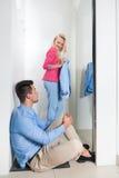 Junge Paar-bemannen kaufender passender Raum-Mode-Shop, das glückliche lächelnde Mädchen, das neue Kleidung versucht, müden Sit O Lizenzfreie Stockfotos